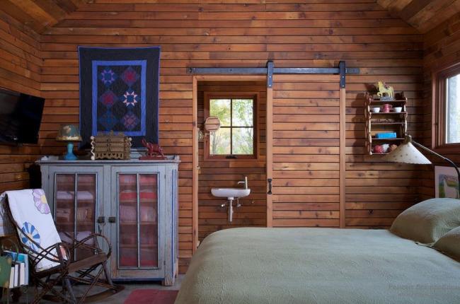 Chambre à coucher de maison de campagne très atmosphérique avec porte coulissante en bois