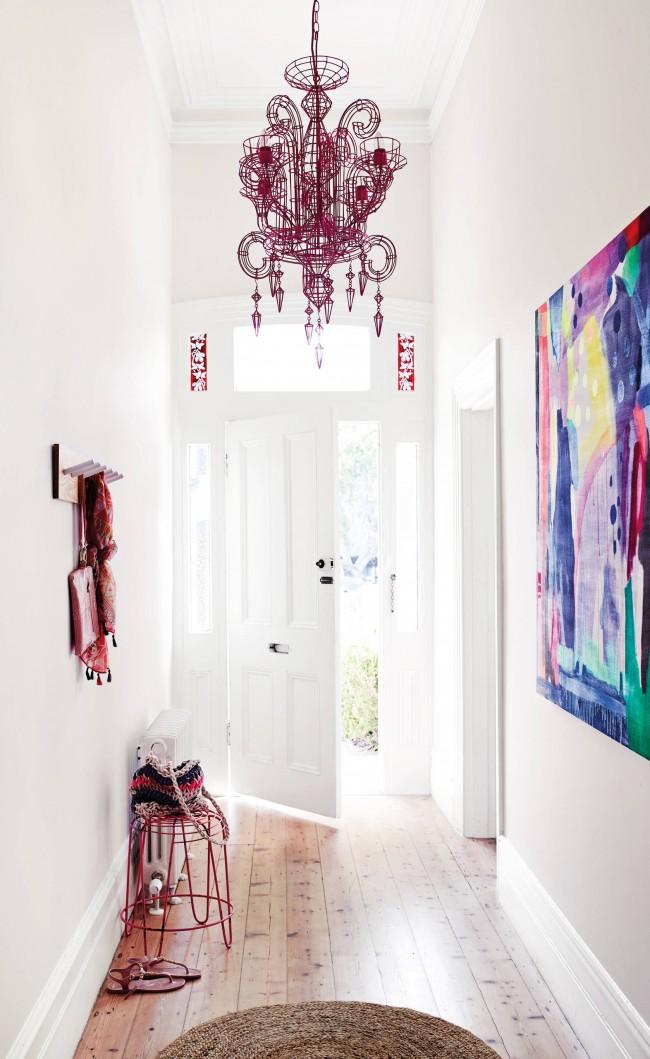 Couloir blanc élégant avec un lustre inhabituel et des accents lumineux sous la forme d'une image