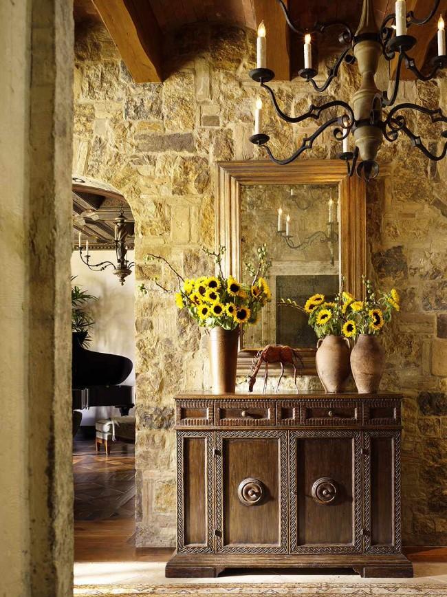 Mur en pierre et poutres apparentes dans le couloir, décoré dans le style de la France médiévale