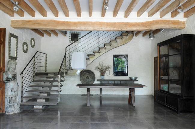 Un contraste éclectique : un escalier sur un limon avec des rampes modernes sur fond antique