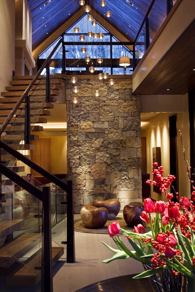 Un hall d'entrée spacieux d'une maison à deux étages.  Éclairage : pendentifs en cristal de Bocci