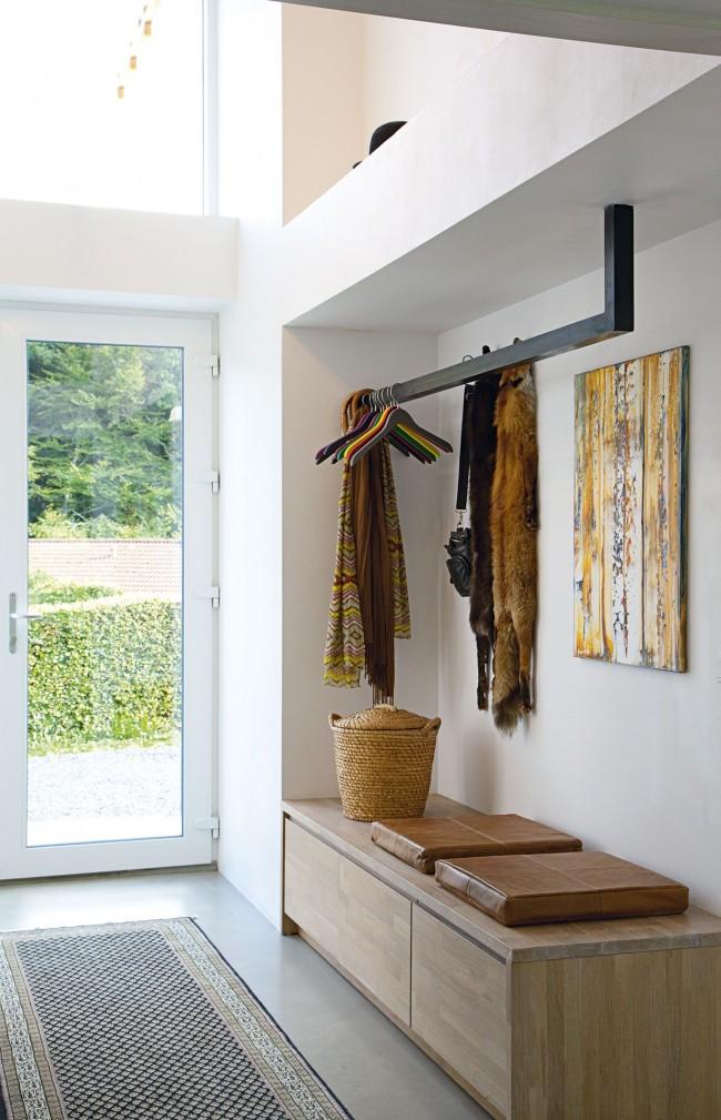 Couloir élégant avec une porte d'entrée en plastique blanc et un cintre minimaliste inhabituel