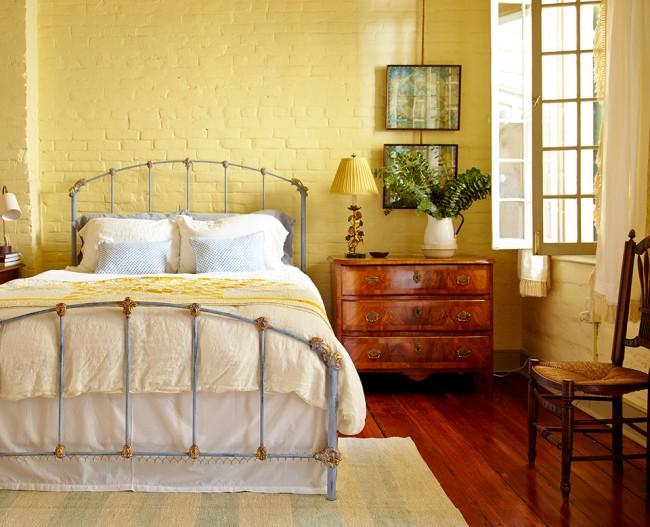 La combinaison parfaite d'un lit en fer forgé et de briques jaunes à l'intérieur de la chambre