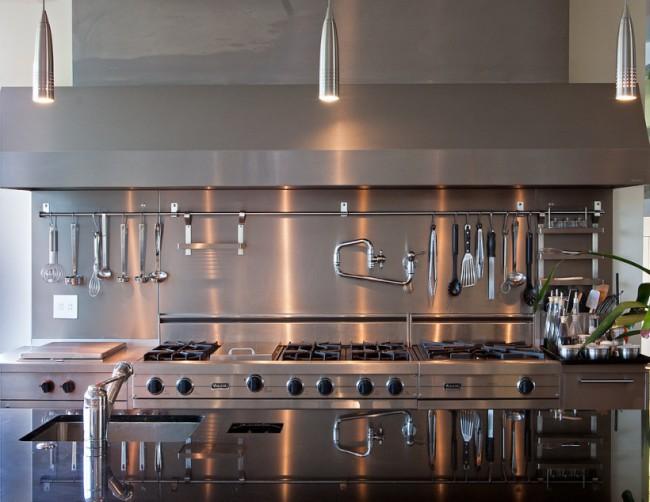 Longue rampe en aluminium dans la cuisine avec armoires, dosseret et plan de travail majoritairement en métal brossé