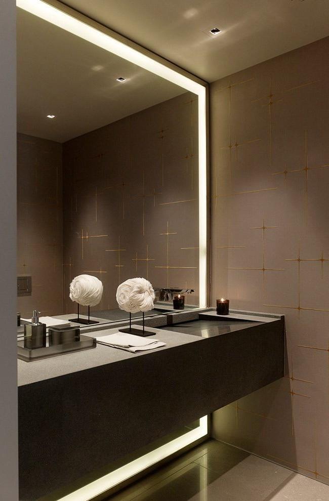 L'éclairage autour du grand miroir, combiné à un plafonnier tamisé, crée une sensation d'intimité, parfaite pour une tenue de soirée