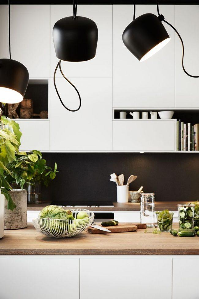 Cuisine moderne contrastée en noir et blanc, associée à un plan de travail en bois