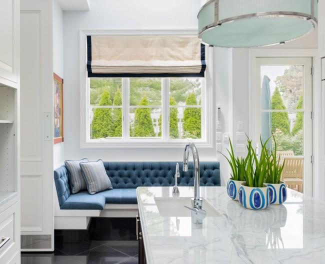 Un canapé au rembourrage bleu sous une grande fenêtre