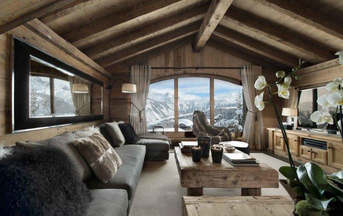 matériaux naturels, décoration murale en bois, poutres au plafond, meubles en bois et coussins en peaux et fourrures