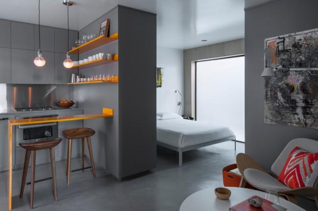 Une combinaison chic de couleurs orange et gris à l'intérieur d'un appartement d'une pièce