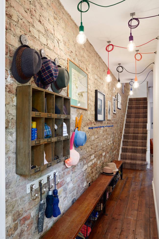 Hall d'entrée dans une maison privée de style loft.  Cheminées, lampes élégantes, étagères ouvertes et un long banc avec espace de rangement