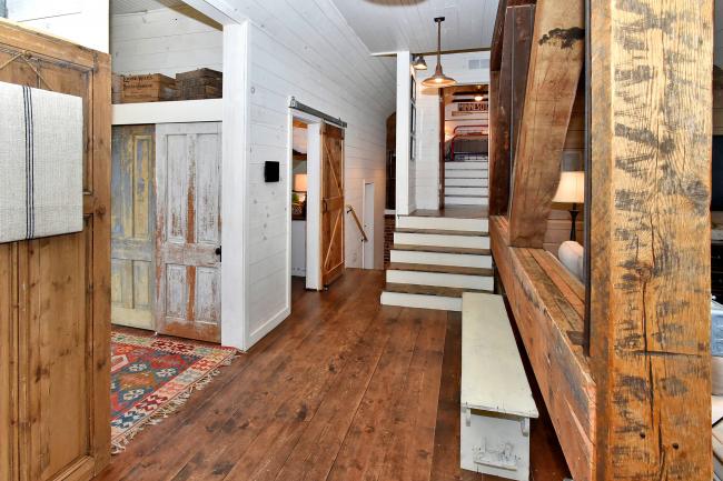 Un hall d'entrée de style loft dans une maison de campagne comporte de nombreux éléments en bois - peints, naturels, vieillis artificiellement