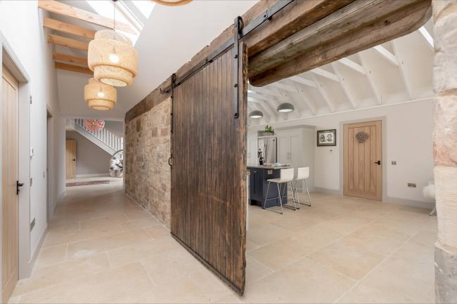 Pierres apparentes aux murs, poutres en bois au plafond dans le couloir