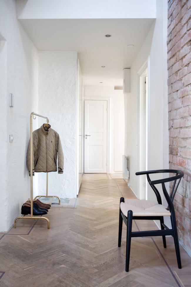 Un hall d'entrée lumineux de style loft pour ceux qui n'aiment pas les contrastes.  Plâtre blanc texturé, sol en frêne et mobilier minimaliste