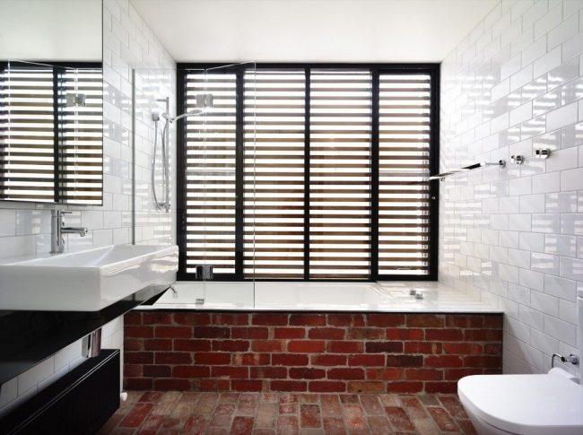 Rideau en verre presque invisible pour une salle de bain d'ambiance avec des éléments de maçonnerie naturelle à l'intérieur