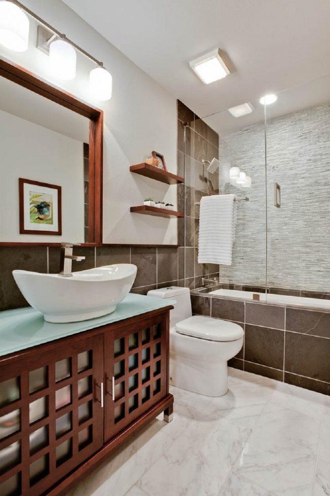 Rideau coulissant en verre dans la salle de bain aux couleurs claires avec des accents lumineux sur des éléments décoratifs en bois naturel