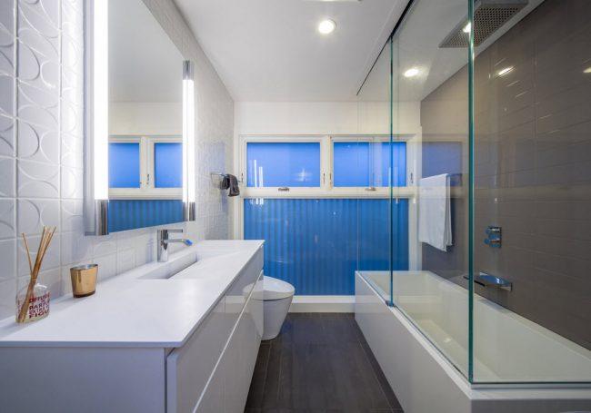 Salle de bain spacieuse avec grand rideau de verre et accents de couleur bleu vif