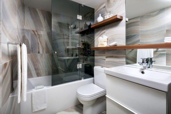 Rideau coulissant en verre teinté foncé pour une salle de bain originale avec des accents sur des étagères en bois naturel