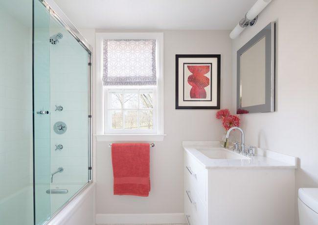 Une salle de bain très soignée avec un rideau coulissant en verre clair et de délicats accents roses sur les éléments de décoration