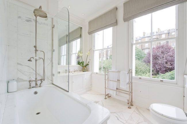 Toile de verre dans une salle de bain délicate dans des tons blancs et stores romains clairs aux fenêtres