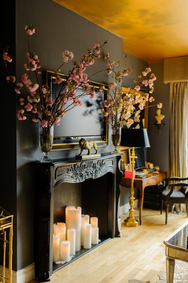 Salon en noir et or avec une fausse cheminée sculptée