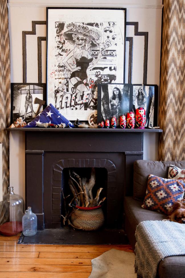 Sur l'étagère de la cheminée se trouve une collection de poupées matriochka, de photographies et de peintures grotesques, et à l'intérieur de la chambre de combustion se trouve un vase en osier avec des branches