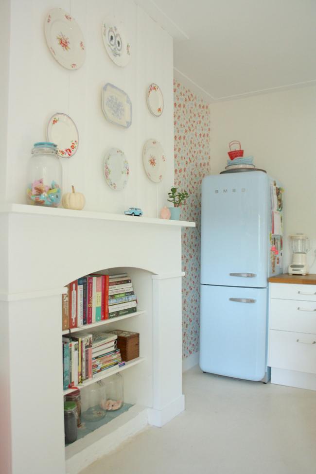 Une cheminée décorative dans la cuisine peut être utilisée comme support, ranger des livres avec des recettes, divers pots de produits en vrac et d'autres petites choses dedans