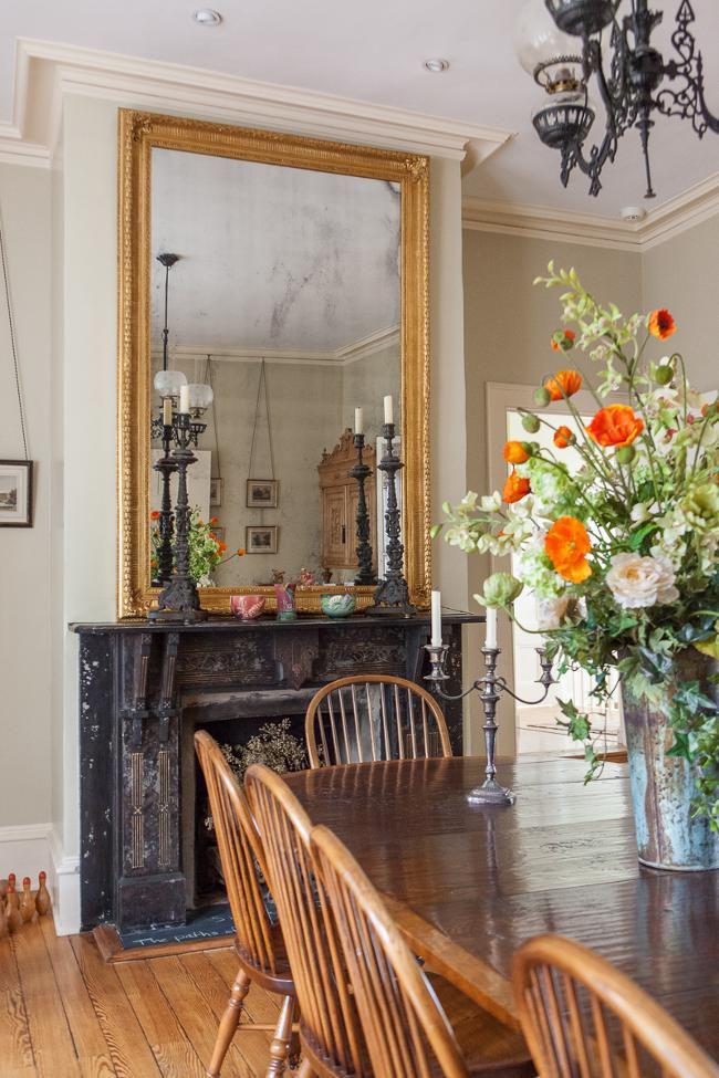 Les fleurs séchées et les chandeliers ont fière allure dans une cheminée ancienne avec une façade minable