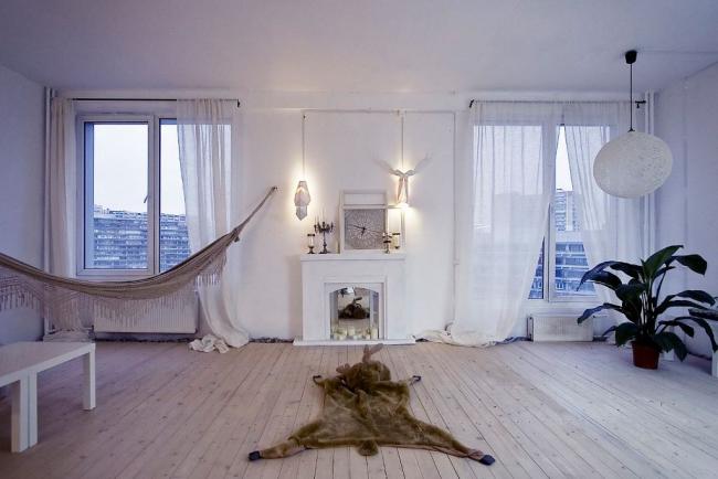 Une salle blanche comme neige avec une cheminée décorative en miroir reflétant des bougies