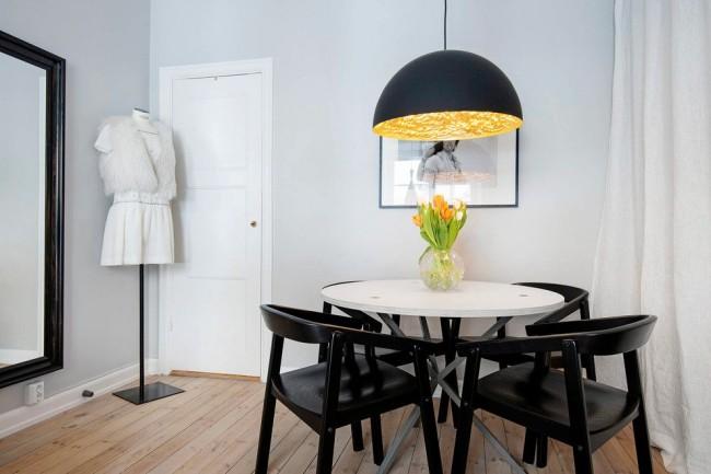 La porte blanche de la salle à manger scandinave gris clair semble assez calme et traditionnelle.