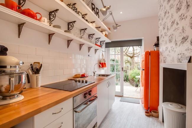 Des étagères ouvertes avec divers objets de décoration servent de décoration à la cuisine