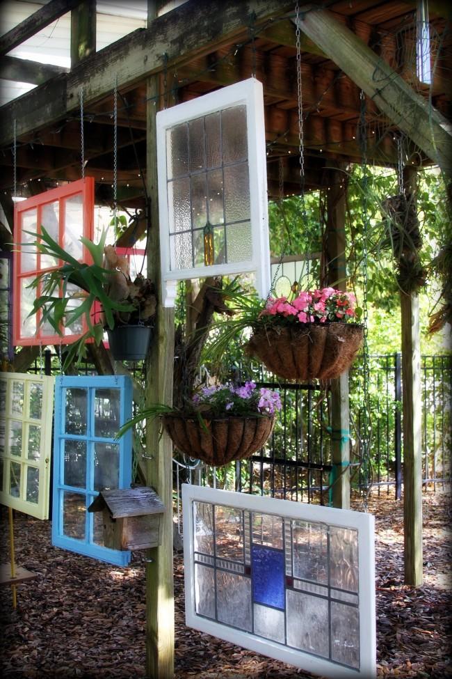 Une composition inhabituelle peut être créée en utilisant de vieilles fenêtres multicolores et des pots de fleurs