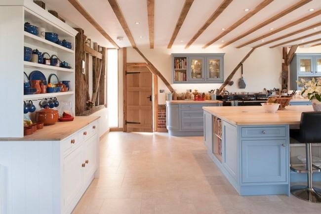 Les poutres brutes au plafond sont plutôt soignées sur fond de murs blancs et de meubles délicats