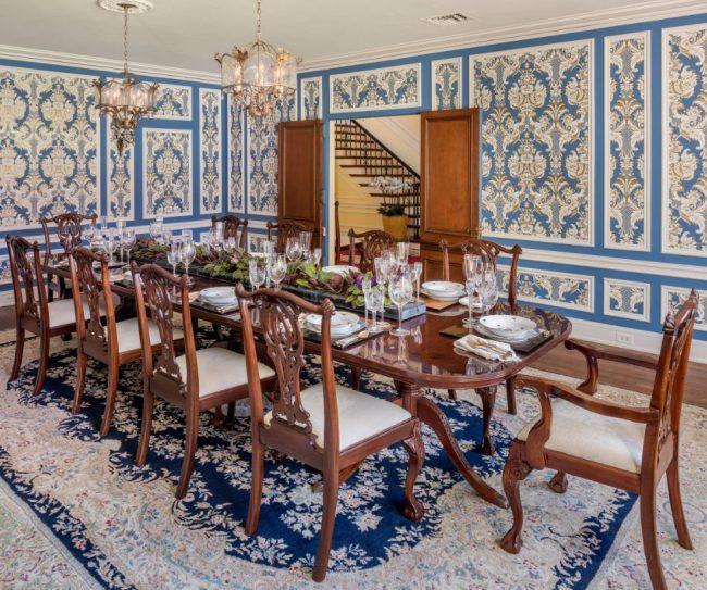 Salon classique dans une maison de campagne : papier peint bleu avec ornements dorés et meubles en chêne