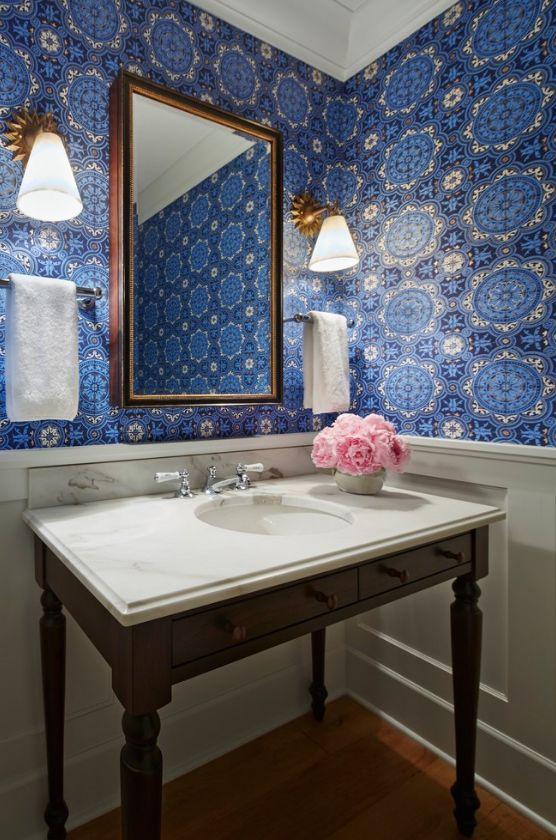 Le papier peint bleu est magnifique dans une salle de bain classique