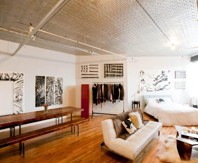 Salon et chambre dans une pièce.  Le style industriel dans la conception d'un studio est un choix fréquent de la jeunesse créative d'aujourd'hui