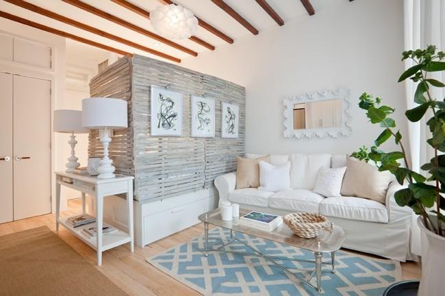 Salon et chambre dans une pièce.  Intérieur de studio blanc frais avec cloison de zonage en matériaux naturels