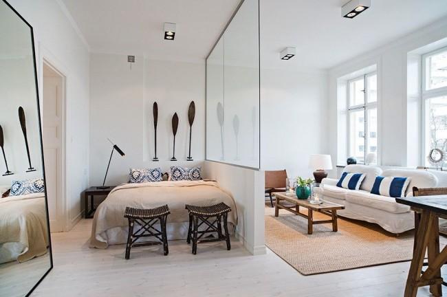 Salon et chambre dans une pièce.  Mur de verre entre la chambre et les espaces publics