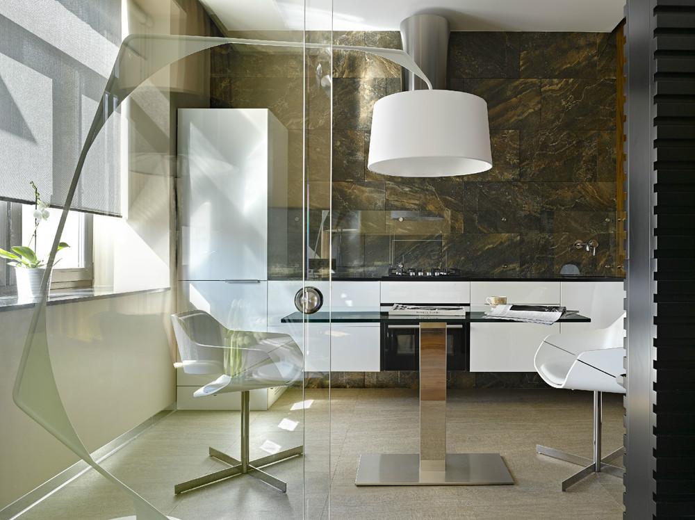 Une autre option pour la protection du verre transparent au-dessus de la surface de travail dans une cuisine moderne et élégante revêtue de pierre naturelle