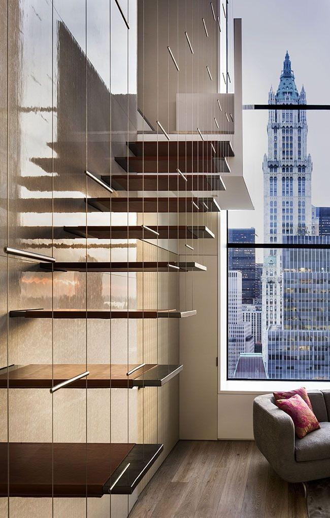 Appartement en duplex avec un escalier en porte-à-faux, visuellement légèrement séparé du reste de l'espace