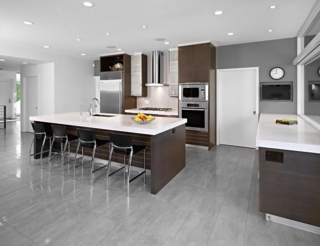 Des meubles blancs avec des fragments de noir sur fond chocolat, des poignées volumineuses, des panneaux de bois mur à mur ou des lampes futuristes contribueront à créer une impression de glamour à l'intérieur de votre cuisine.