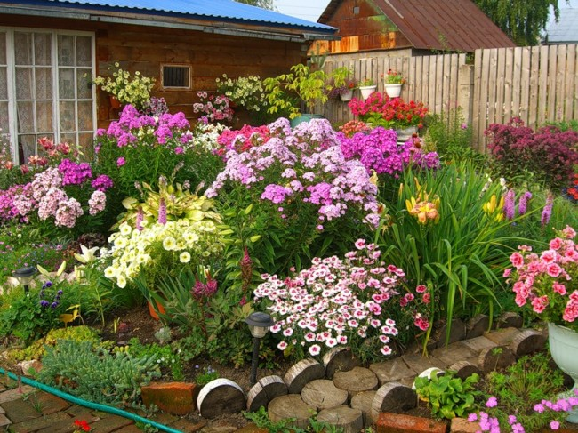 Clôture pour les parterres de fleurs de vos propres mains.  Les sections transversales des bûches peuvent être enterrées ou posées à votre guise, par exemple en mosaïque