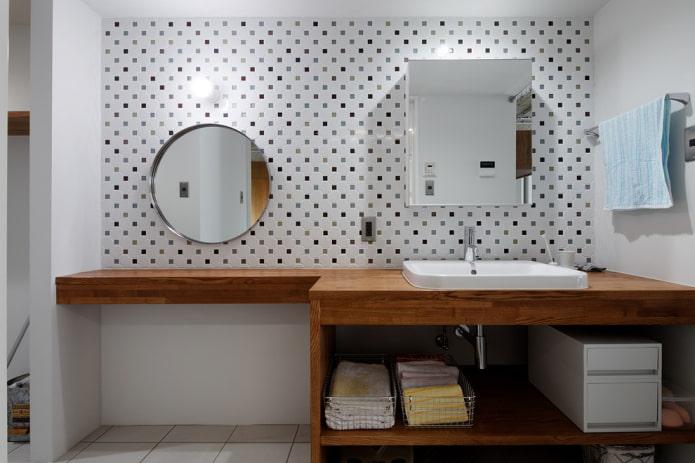 deux miroirs sur le mur à l'intérieur de la salle de bain