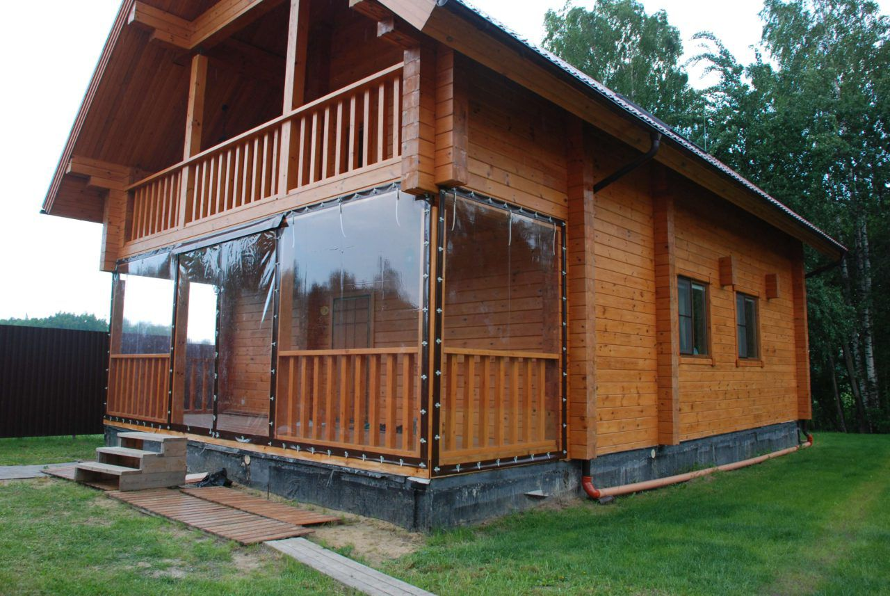 La terrasse spacieuse est isolée avec des rideaux en PVC pour correspondre à la finition du bois