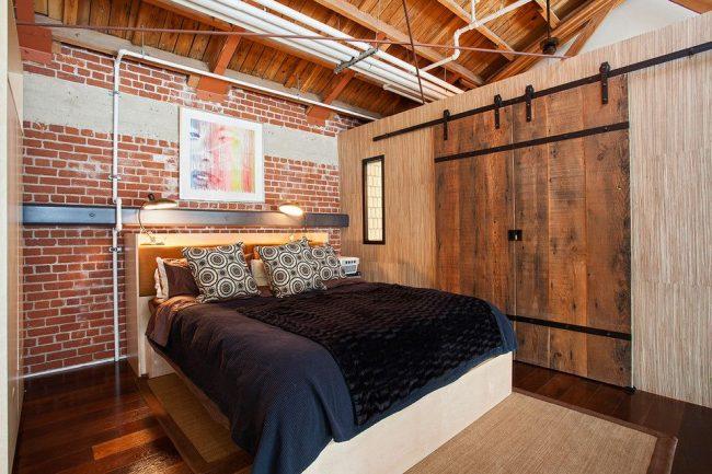 Mur de briques et portes en planches de bois dans une chambre de style loft