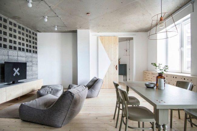 Salon lumineux avec plafond en béton et porte en bois