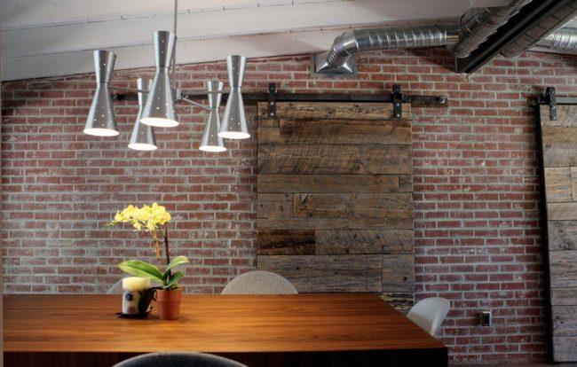 Porte en bois, tuyaux de ventilation ouverts et mur de briques à l'intérieur du loft
