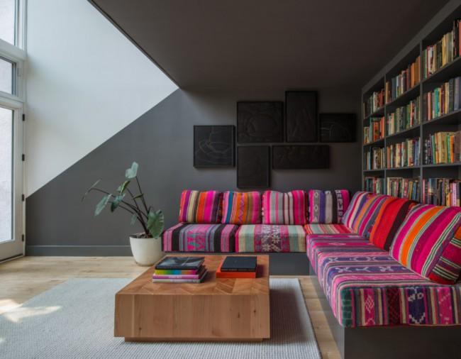 Mobilier moelleux pour le hall.  Des tons de fond stricts de décoration et des motifs ethniques lumineux dans des meubles rembourrés