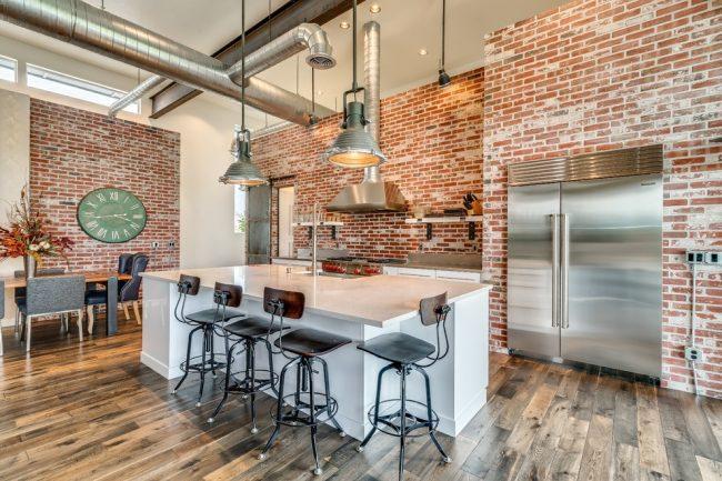 Excellente combinaison de mur de briques avec un mobilier design et un décor de cuisine moderne