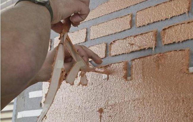 Ruban de masquage dans le travail sur l'imitation de la maçonnerie sur les murs