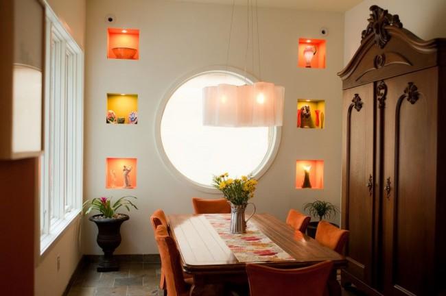 Dans une petite salle à manger, petites niches dans le mur avec décorations et éclairage